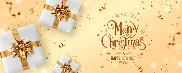Fototapete - Gold Christmas and New Year Text on gold Xmas background with gift boxes, fir branches, gold ribbon, decoration, sparkles