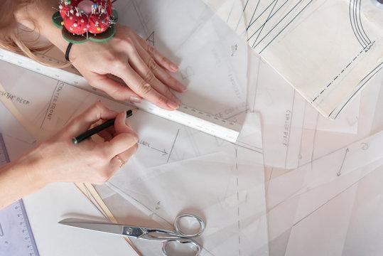 Flat lay woman fashion designer working on sewing patterns.
