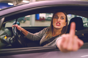Young woman driver showing middle finger trough the window of the car mad angry furious pissed on the parking in the city at night driving