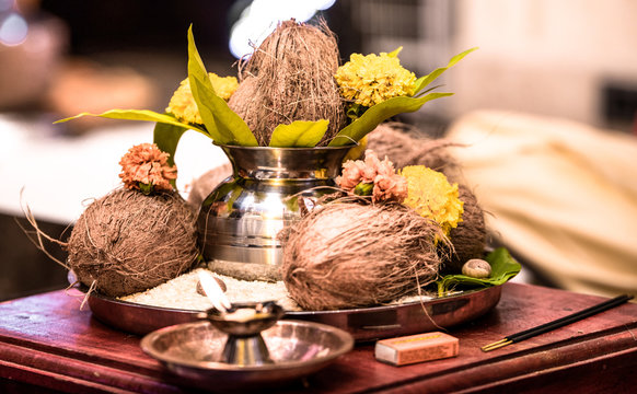 Beautiful photo from India of Pooja Thaali (Praying Tray) kept ready as an offering to God for traditional Hindu prayer ceremony. Tray consists coconut, stainless urn of holy water, marigold, rice etc