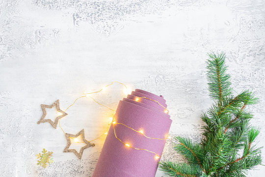 Rolled  sport mat with  festive decoration  Christmas best gift for active people concept.  Yoga xmas background. Copy space