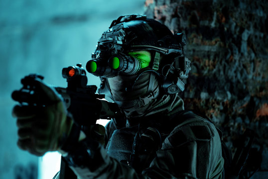 Man in uniform with machine gun and turned on night vision device beside brick wall. Closeup airsoft soldier with green light on face in night