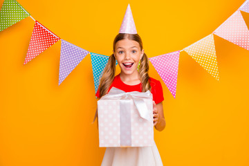Can I open box. Photo of pretty amazed small lady long tails hairstyle celebrating birthday party hold big giftbox wear paper hat casual red white dress isolated yellow color background