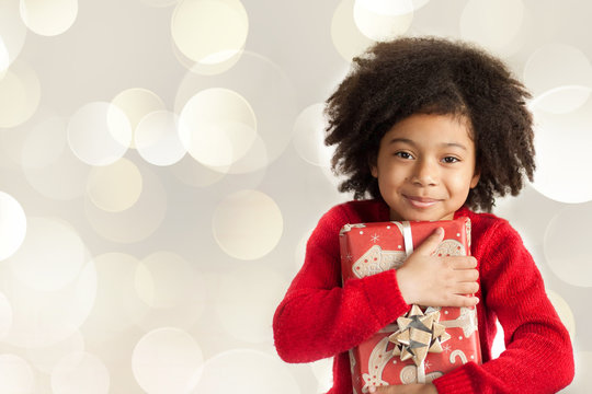 Christmas concept. Happy adorable african american child girl with christmas gift in hands isolated on white background.