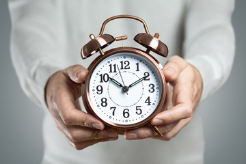 Retro clock held by hands of a man