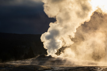 Old Faithful geyser exploded smoke with warm sunlight in early morning.