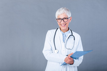 Happy smiling senior female doctor writing on clipboard, isolated on background. Medicine and health care concept. Smiling mature medical doctor woman with stethoscope.