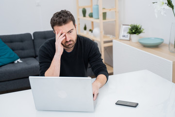 Stressed and worried man at home office
