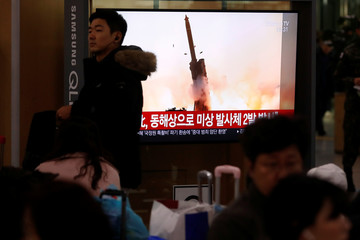 People watch a TV broadcasting file footage for a news report on North Korea firing an unidentified projectile, in Seoul