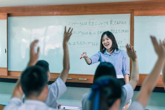 """An Asian female teacher is teaching Japanese. The meaning of texts are """"Mr. Suriya bought a shirt for the teacher, Mr Ittithep taught me Japanese, I have been taught Japanese from Mr Athithep""""."""