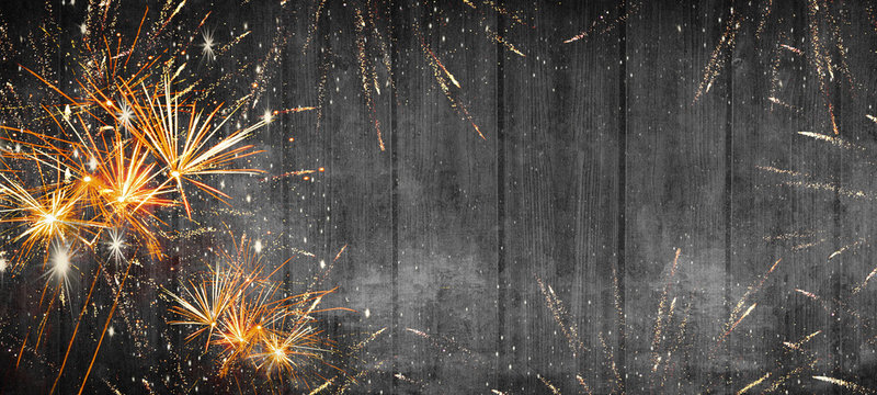 Silvester background banner - Frame made of firework and stars in the night silvester new year party on black rustic wooden texture, with space for text