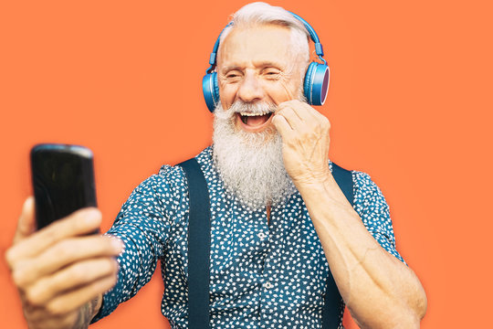 Senior bearded man taking selfie with mobile phone while listening favorite playlist with headphones - Trendy hipster male having fun with smartphone social apps outdoor - Elderly, technology concept