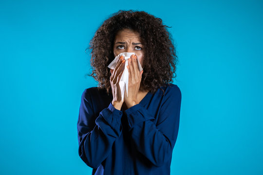 Young girl with afro hair sneezes into tissue. Isolated woman is sick, has a cold or has allergic reaction. Health, medicine, illness, treatment concept