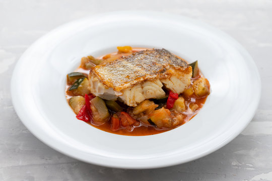 cod fish with vegetables in white plate
