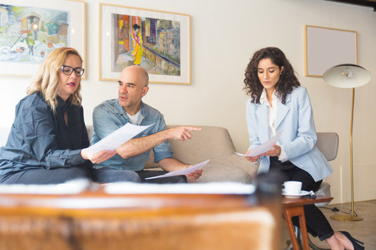 Middle aged couple meeting with notary and reading documents. Man and women sitting in living room at home and talking. Legal expert consulting concept