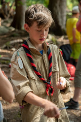 boy scout with a pocket knife in the forest
