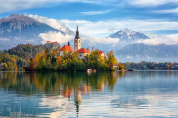 Famous alpine Bled lake (Blejsko jezero) in Slovenia, amazing autumn landscape. Scenic view of the lake, island with church, Bled castle, mountains and blue sky with clouds, outdoor travel background Fotomurales