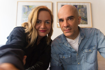 Joyful worried middle aged couple taking selfie at home. Caucasian man and woman in casual looking at camera, smiling. Selfie or video call concept