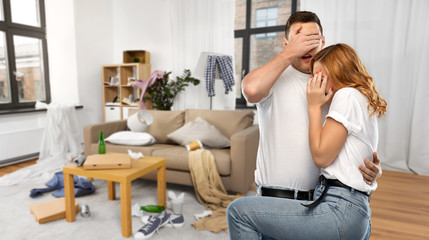 household, cleaning and domestic life concept - scared couple in white t-shirts over messy home...