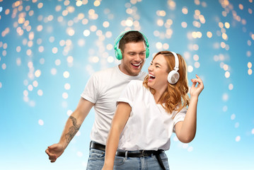 music, technology and people concept - portrait of happy couple in white t-shirts and headphones dancing over holidays lights on blue background