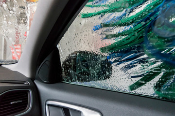 The auto is driving inside a carwash tunnel, view from a car. Robots-brushes in a car wash service.