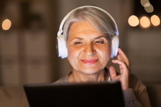 technology, people and lifestyle concept - happy senior woman in headphones and tablet pc computer listening to music at home in evening