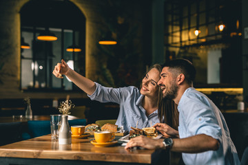 couple taking picture while eating in restaurant