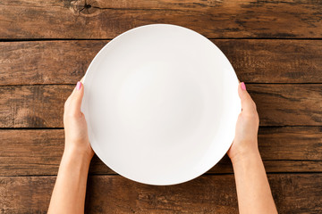 Woman's hands holding empty white plate over rustic wooden table. Top view
