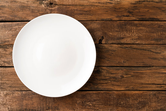 Empty white dish on rustic wooden table. Top view