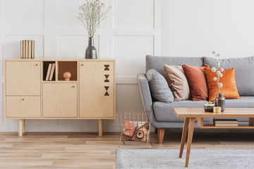 Wooden furniture and grey scandinavian sofa with pillows in beautiful living room interior Fotomurales