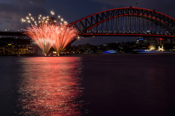 Red stars fireworks in Sydney Harbour with boats and parks lights behind. Australia.