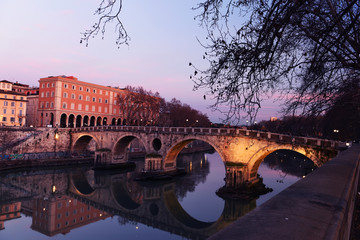 Fotobehang - Evening on the embankment by the Tiber River. Rome. Italy. Urban landscape of bridges across the river.