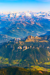 Aerial view on the Swiss Alps with green valley and snow peaks, Switzerland