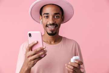 Photo of smiling african american man using cellphone and earpods