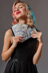 Blonde girl in black stylish dress holding some money, posing against gray background. Gambling entertainment, poker, casino. Close-up.