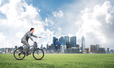 Businessman with paper documents in hand on bike