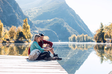 Two travel hikers using mobile phone while sitting in front of the lake in mountain.