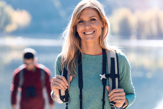 Pretty young female hiker smiling while looking at camera in front of lake.