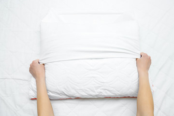 Woman hands on mattress surface changing white cotton cover on pillow. Regular bed linen change. Closeup. Point of view shot. Top down view.