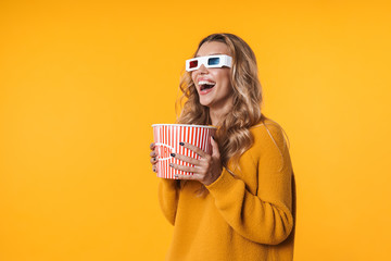 Image of woman in 3D glasses holding popcorn bucket while watching movie