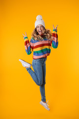 Full length image of blonde woman in winter hat showing peace fingers