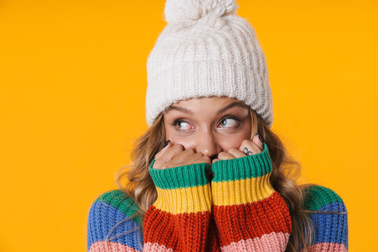 Image of frozen blonde woman in winter hat staying warm in her sweater