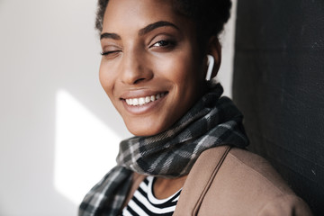 Portrait of african american smiling woman winking and using earpod
