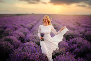 Young woman in white dress walks through blooming lavender field at sunset