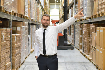 portrait friendly businessman/ manager in suit working in the warehouse of a company