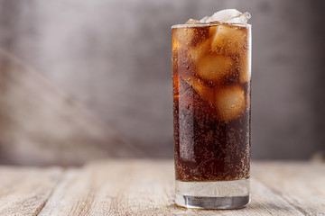 Cola with Ice Cubes. Glass of cola with ice cubes on wood table, soft drink. Copy Space.