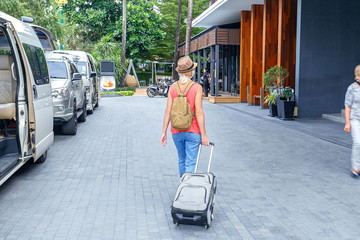 Tourist woman traveling in Thailand and walking with suitcase on city street. Arrive in hotel. Travel concept.