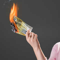 Smiling girl burns money. Concept of extravagance