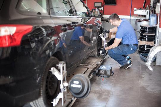 Wheel alignment. Car mechanic installing sensor during suspension adjustment
