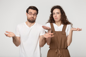 Confused millennial couple shrug shoulders feel baffled